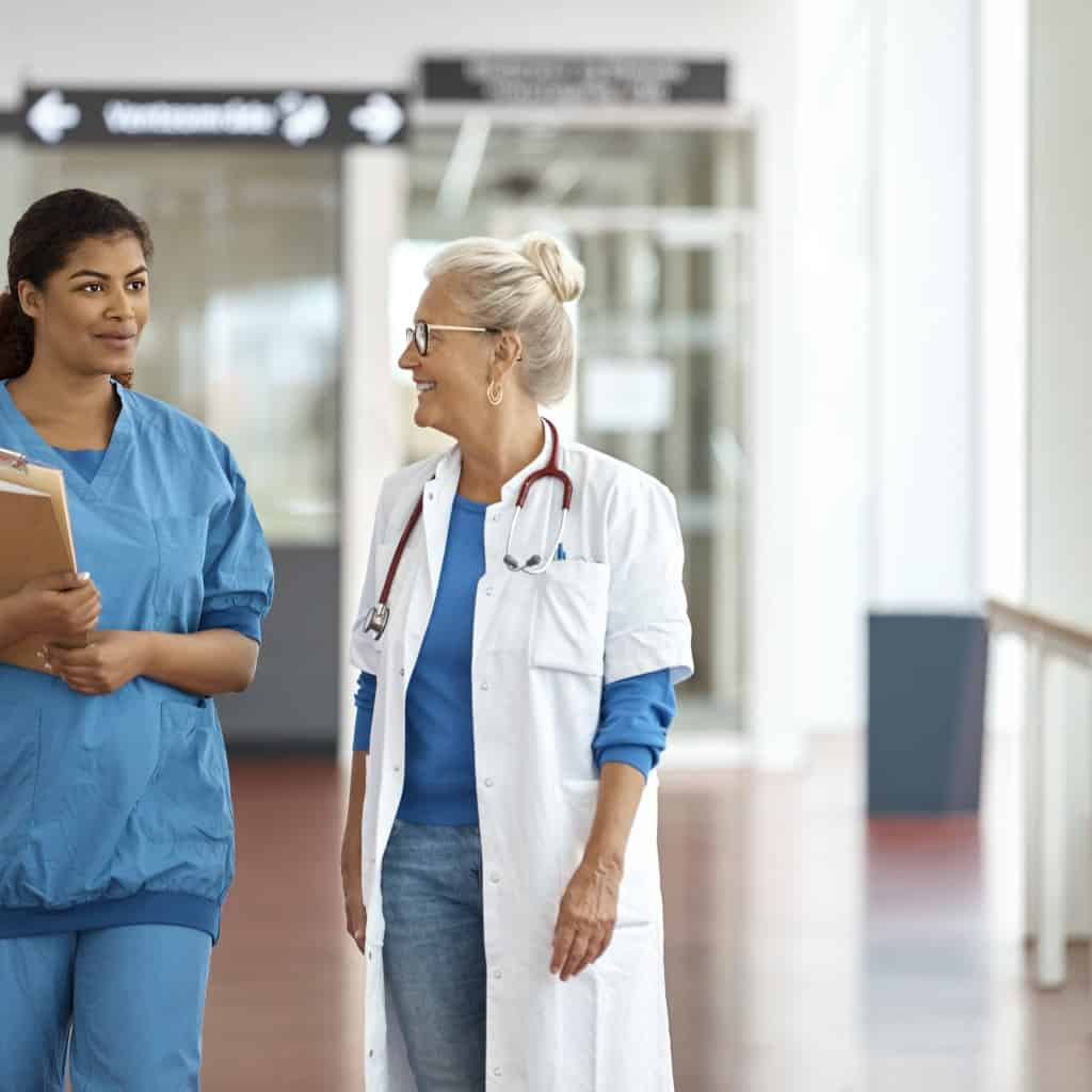 Female nurse talking with doctor while walking in corridor. Medical professionals are discussing in hospital. They are in uniform.